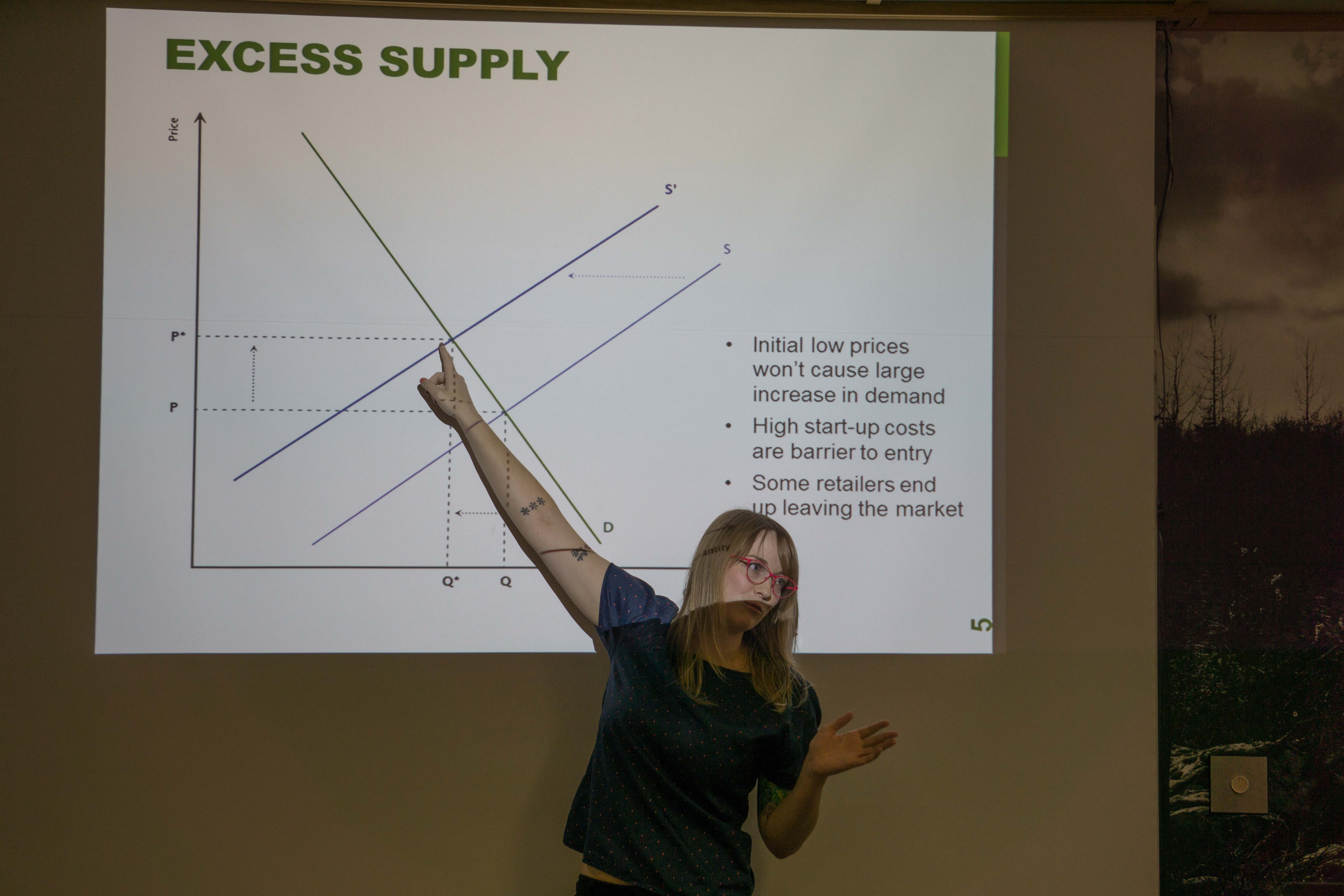 Carole Triem explains a slide about the supply and demand for marijuana retail stores. Triem, who's educated in economics and public policy, wrote a white paper on the topic. (Photo by Jeremy Hsieh/KTOO)