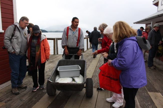 An employee in uniform answers tourists questions about halibut being wheeled around the boardwalk. (Photo by Elizabeth Jenkins/KTOO)