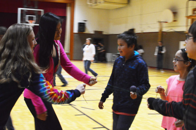 Hoonah students balance a small ball on two strings as a part of a team building exercise. (Photo by Lakeidra Chavis/ KTOO)