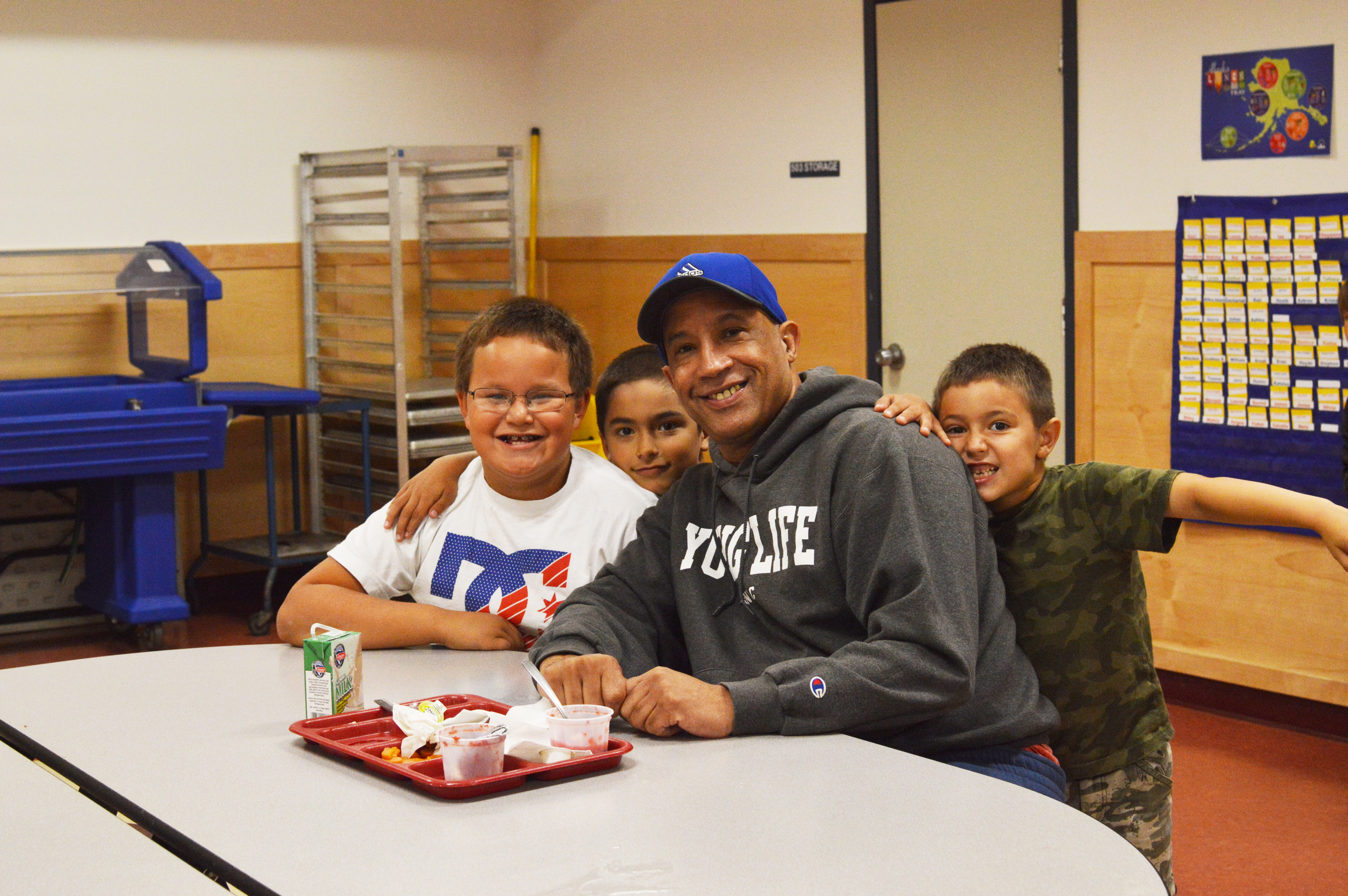 Coach Andy Lee poses with Hoonah kindergartners during their lunch house. (Photo by Lakeidra Chavis/KTOO)