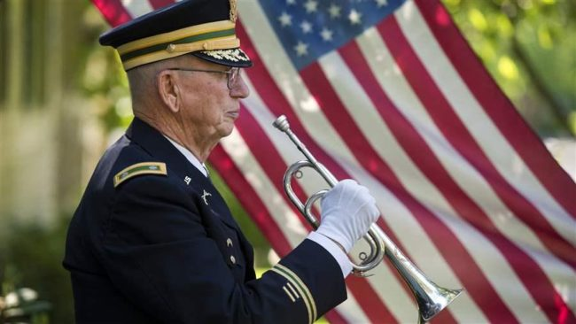 Retired Army Reserve Lt. Col. Philip Kowzan of Spokane, Washington, plays taps at a military honor funeral. States are competing to lower income taxes on military pensions to attract retirees. (AP)