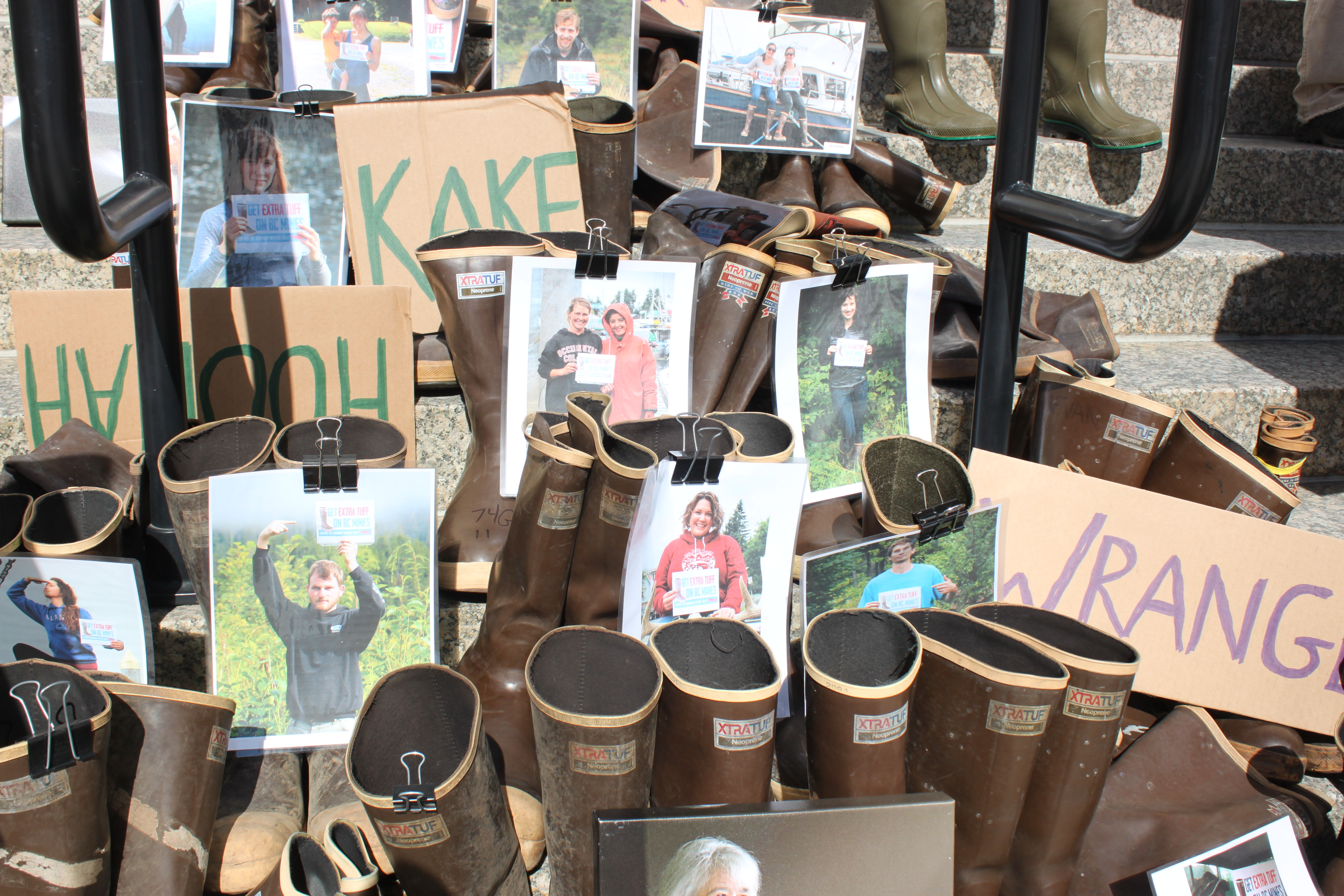Pictures of Southeast Alaska residents and about a hundred pairs of Xtratuf boots lined the Capitol steps. (Photo by Lisa Phu/KTOO)