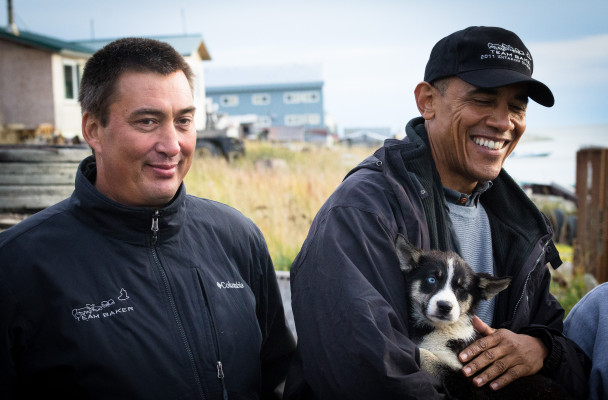 Iditarod musher John Baker meets President Barack Obama in Kotzebue, while Obama holds sled dog puppy Feather. (Photo by Matthew Smith/KNOM)