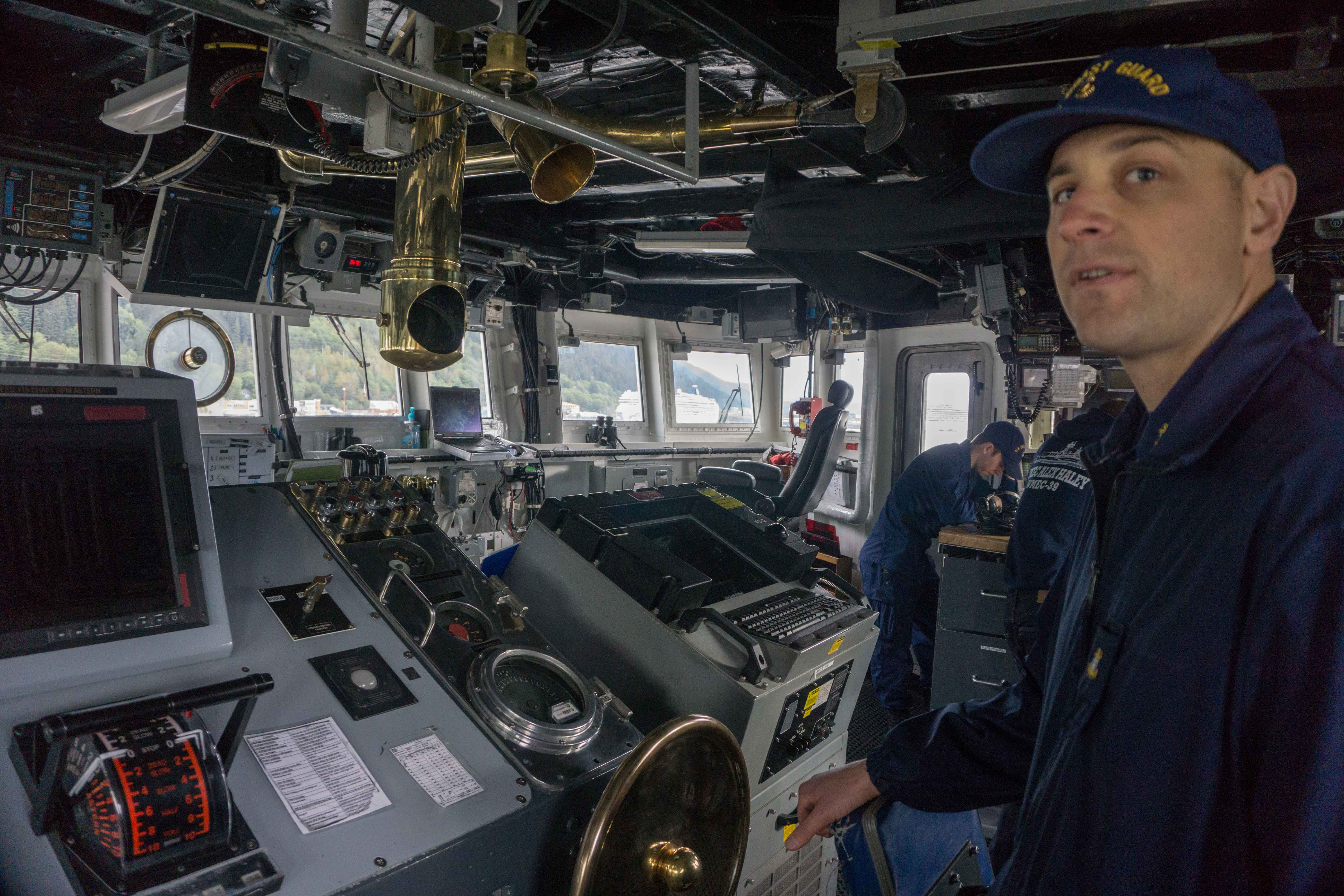 Chief Boatswain's mate Corey Bradshaw at the helm of the Coast Guard Cutter Alex Haley. (Photo by Jeremy Hsieh/KTOO)