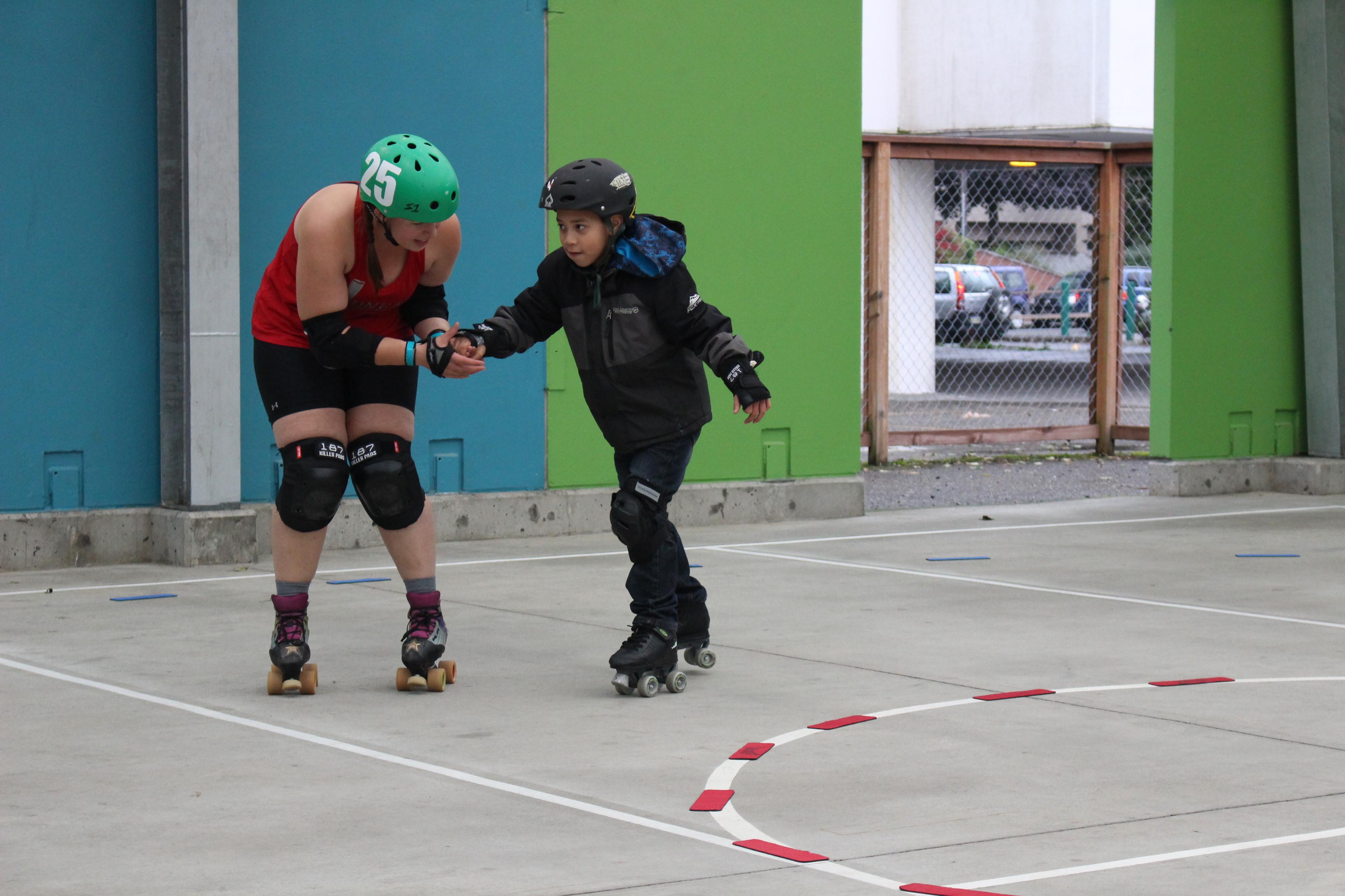 Stephanie Kruse guides a kid around the track. (Photo by Elizabeth Jenkins/KTOO)