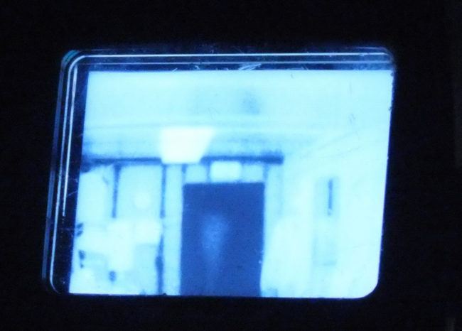 Thermal Imaging Camera or TIC can be used to detect a heat source hidden inside walls or find a victim in a dark, smoky room. Cooler objects, like the exterior door shown in the center of this viewfinder's image, appear as dark or black. Warmer objects, such as the recently turned off ceiling light fixture, show up as bright white. (Photo by Matt Miller/KTOO)