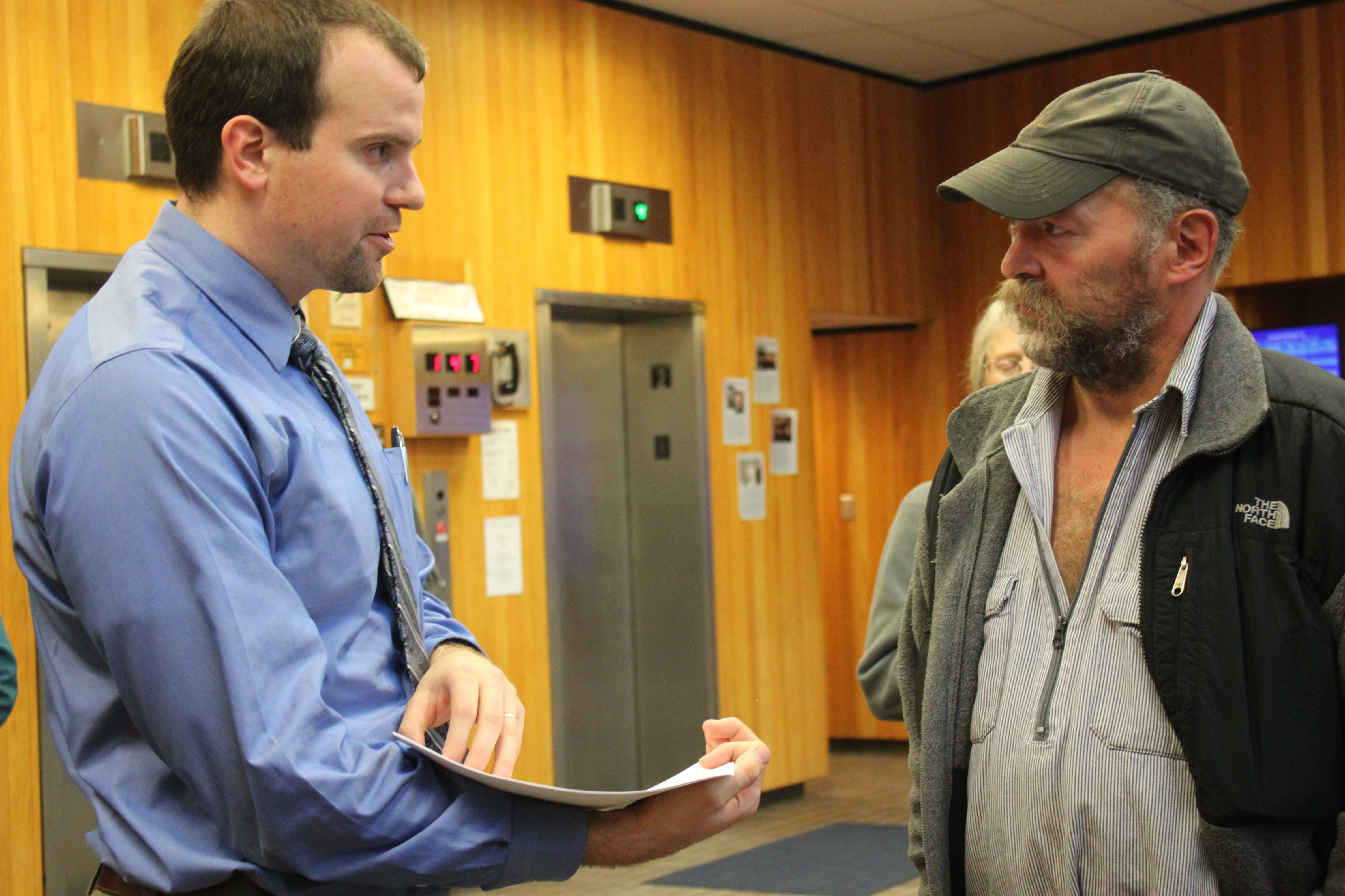 In the lobby of the Dimond Courthourse Monday morning, attorney Nick Polasky hands trapper John Forrest court documents before the trial. Polasky is Kathleen Turley's lawyer. (Photo by Lisa Phu/KTOO)