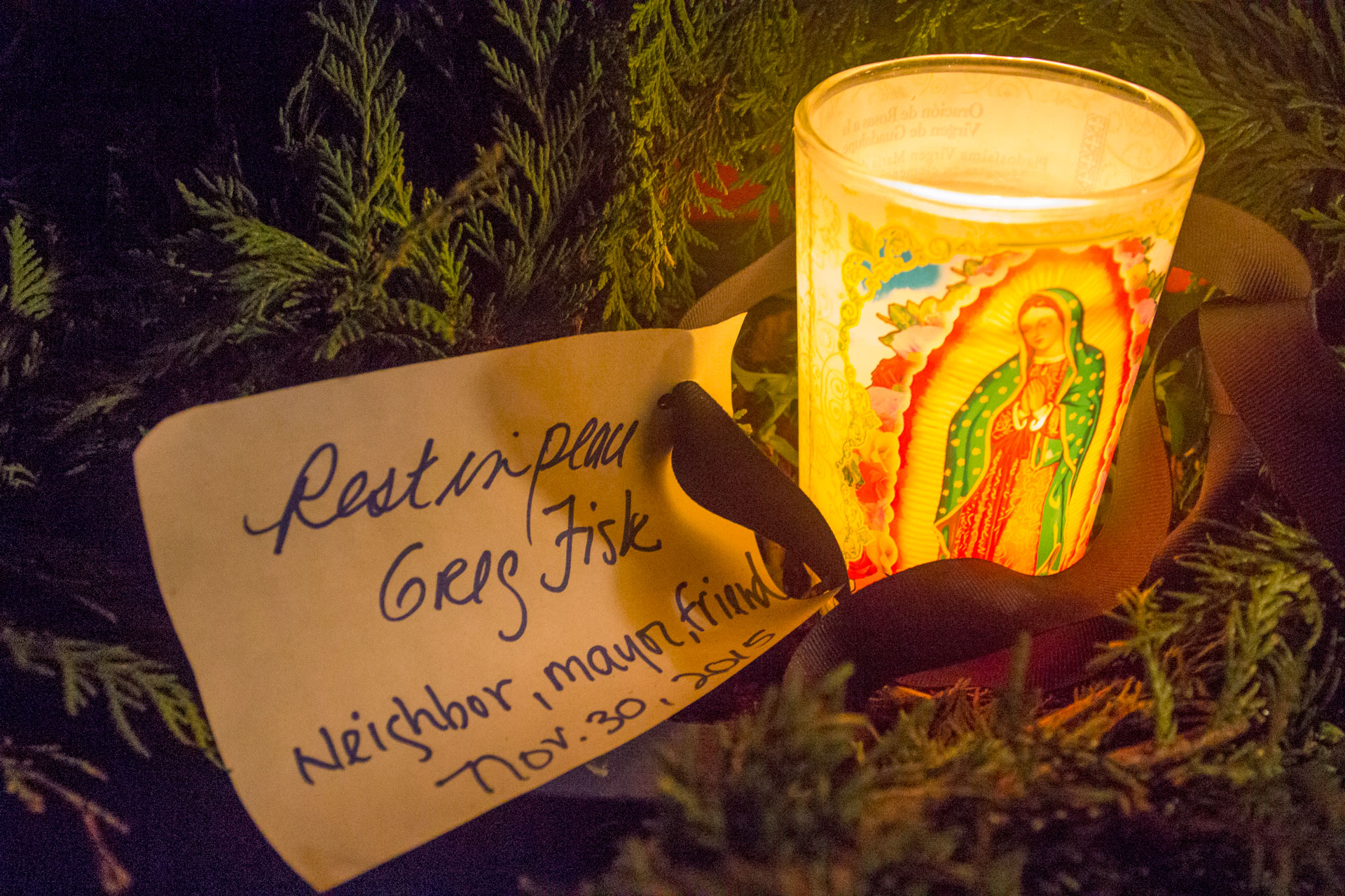 "A candle and a note reading ""Rest in peace Greg Fisk. Neighbor, mayor, friend. Nov. 30, 2015"" outside a neighbor's house on Kennedy St. Monday evening. (Photo by Mikko Wilson/KTOO)"