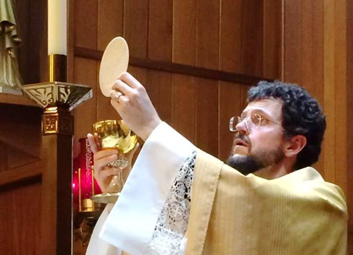 The Rev. Thomas Weise, who serves Catholic churches in Petersburg and Wrangell, celebrates communion during an Easter Vigil. (Photo courtesy Diocese of Juneau)