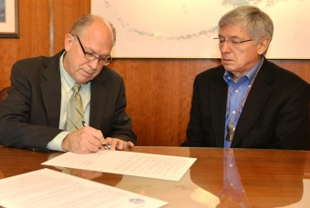 Gov. Bill Walker signs a memorandum of understanding with British Columbia Wednesday as Lt. Gov. Byron Mallott watches. (Photo courtesy governor's office)