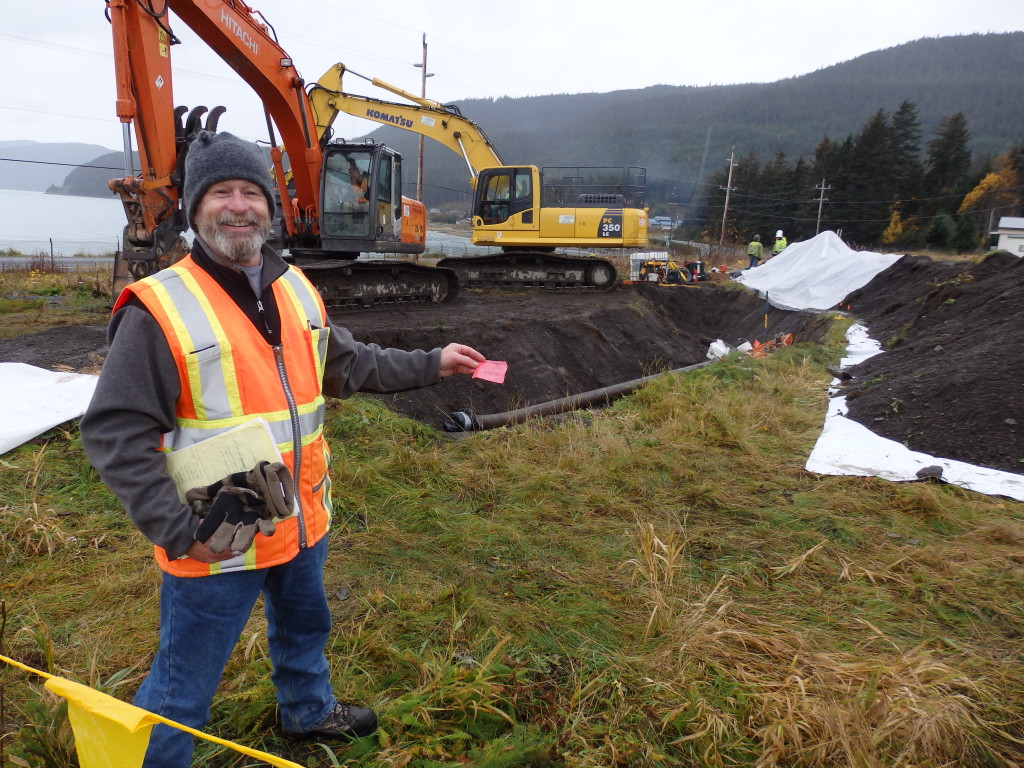 Army environmental protection specialist Brian Adams holds a flag that marks one of the soil testing sites at the fuel terminal admin area in October. (Photo by Emily Files/KHNS)