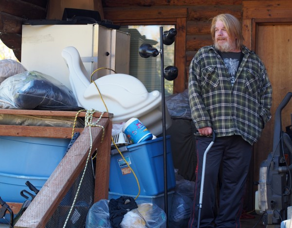 Scott Harrison standing outside the cabin he rents in Big Lake. It's too small inside for him to fit many of his possessions, so he keeps more durable items like clothes and dry-goods outside. (Photo by Zachariah Hughes/KSKA)