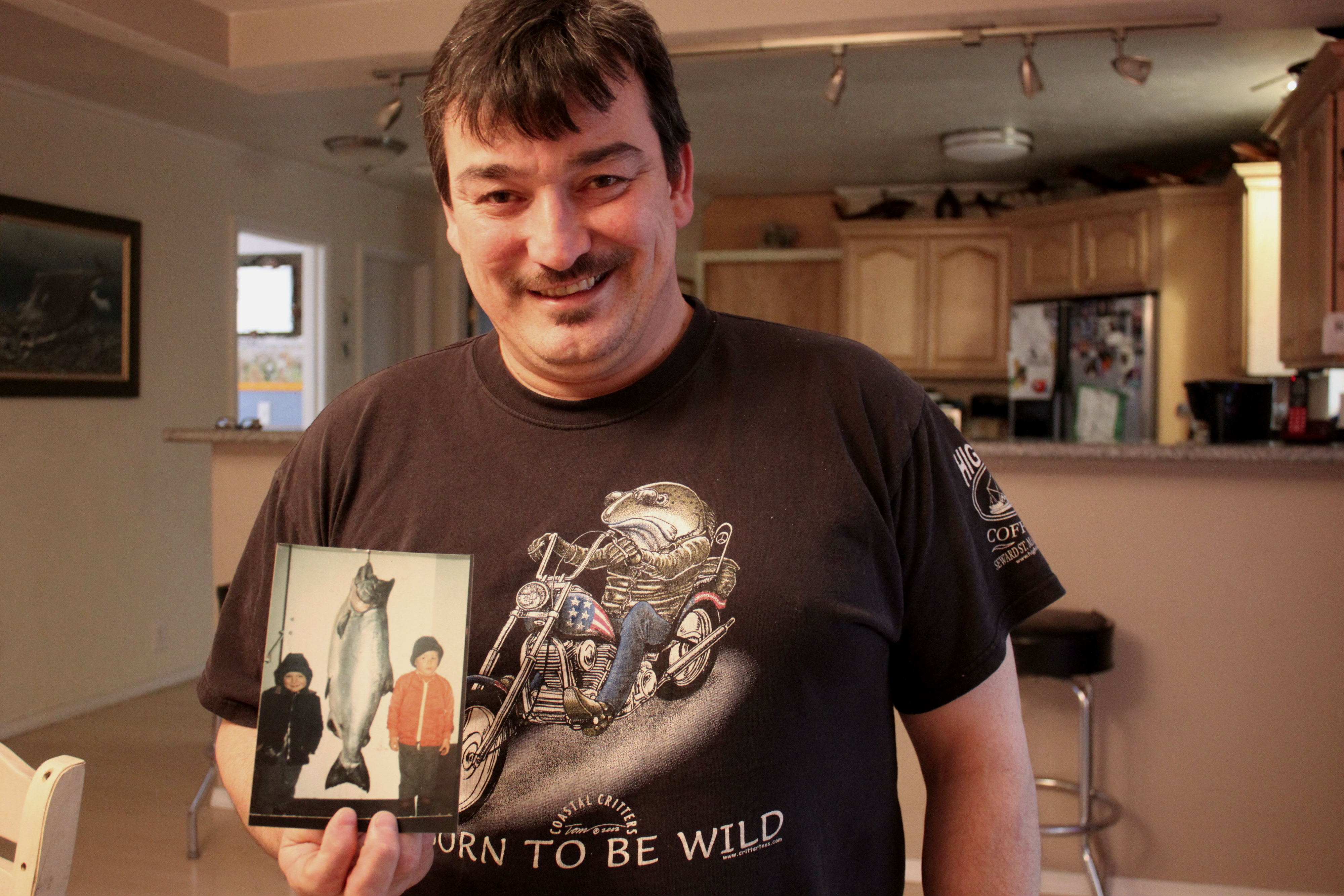 Rob Kenney holds a picture of him and his brother next to a king salmon. (Photo by Lisa Phu/KTOO)