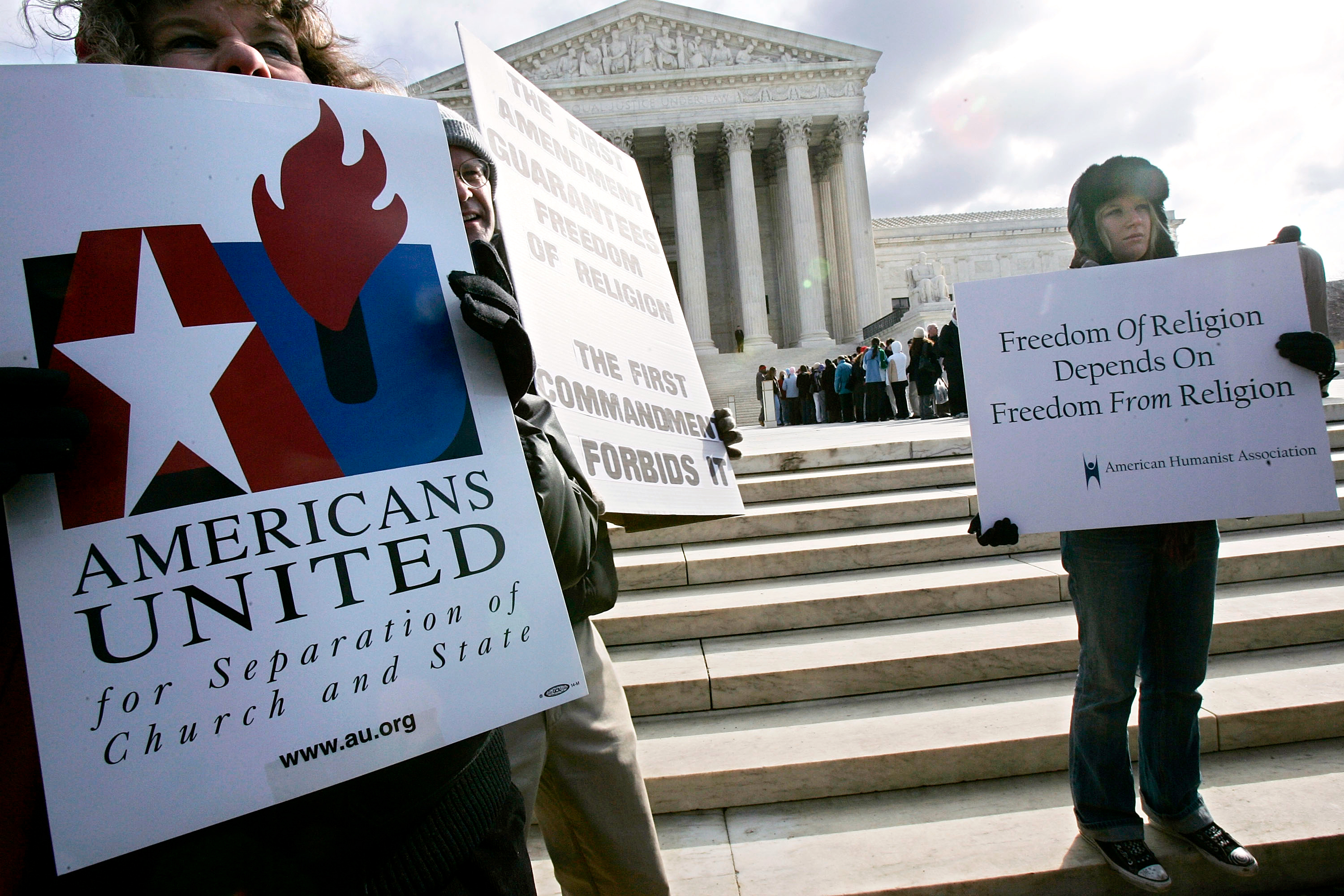 Activists hold posters during a March 2005 rally in front of the U.S. Supreme Court to support separation of church and state. The court heard two cases regarding whether Ten Commandments monuments should be displayed on government properties. Alex Wong/Getty Images