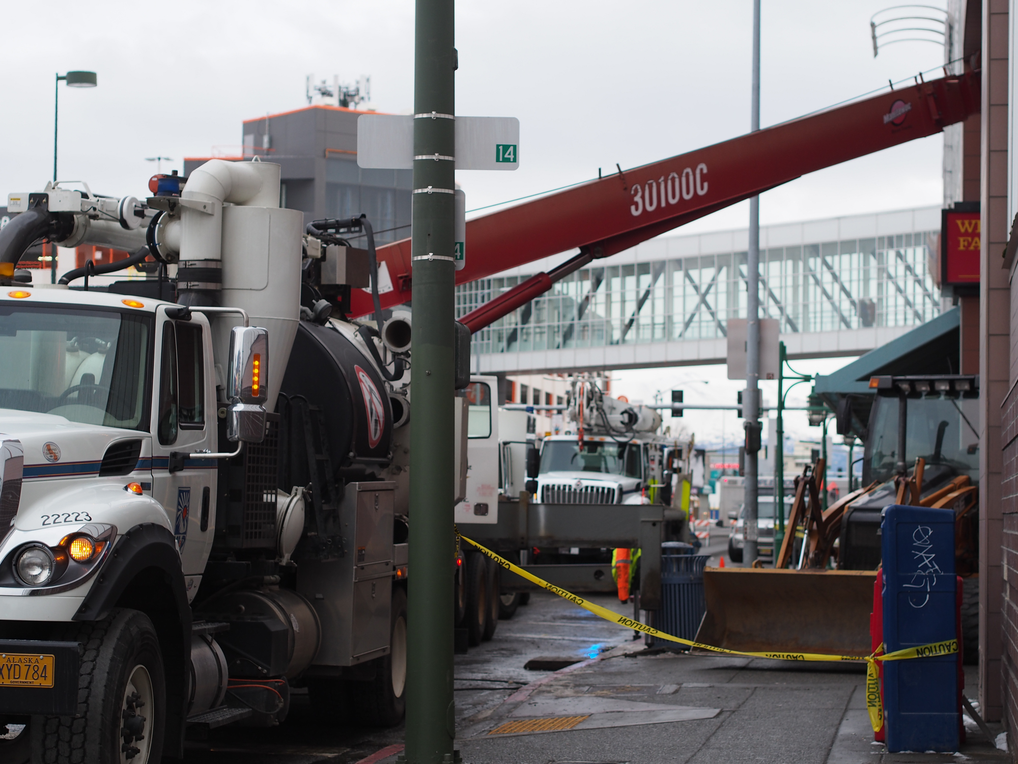 Municipal Light and Power crews work on digging through cement to reach a malfunctioning transformer knocked out during the earthquake, interrupting power to the 5th Avenue Mall. (Photo by Zachariah Hughes/KSKA)