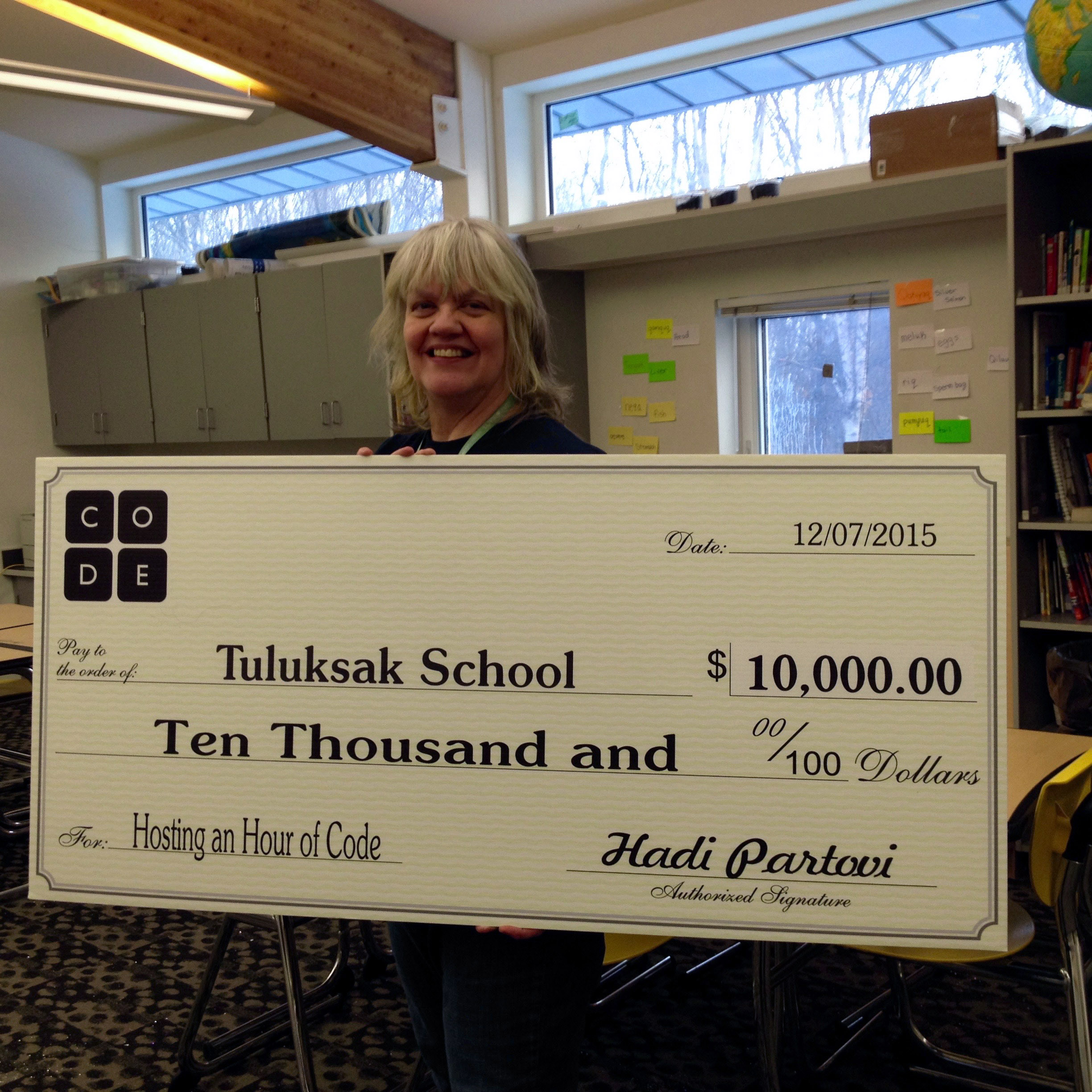 Katherine Garrison holding the check from Code.org inside her Tuluksak classroom. (Photo by Anna Rose MacArthur/KYUK)
