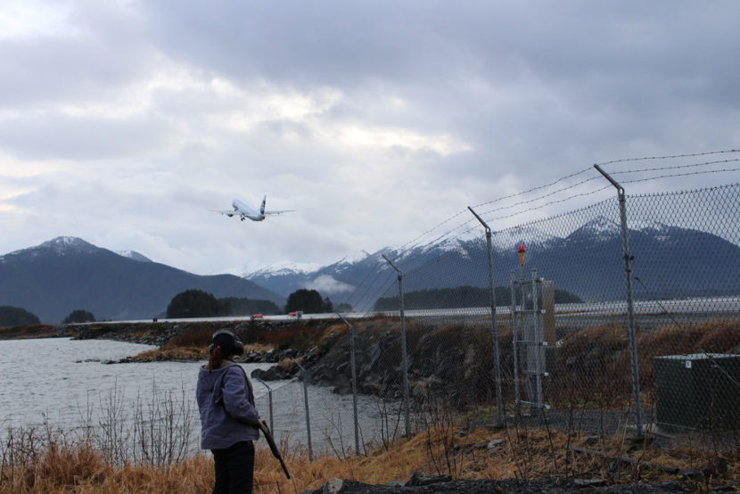 Between Delta and Alaska Airlines, over half a dozen flights come into and out of Sitka daily. After clearing the runway of some ducks, Bauscher looks on as a plane takes off. (Photo by Emily Kwong/KCAW photo)