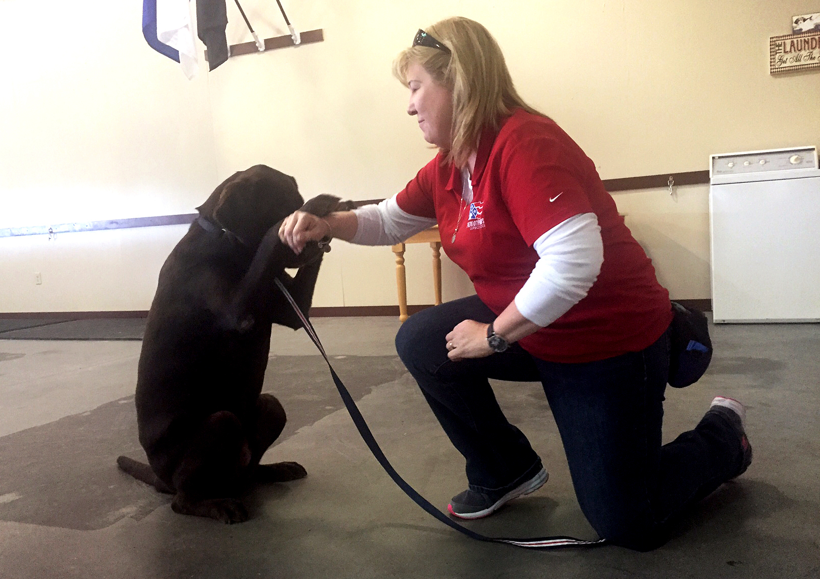 Cheryl Woolnough, director of training at Patriot PAWS in Rockwall, Texas, works with Papi, a Labrador retriever. Lauren Silverman/KERA News