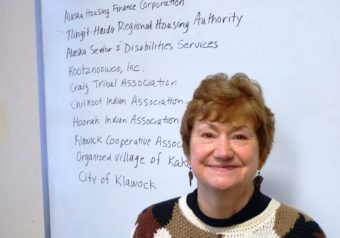 Southeast Senior Services Director Marianne Mills poses with a list of other organizations it works with. (Photo by Ed Schoenfeld,/CoastAlaska News)
