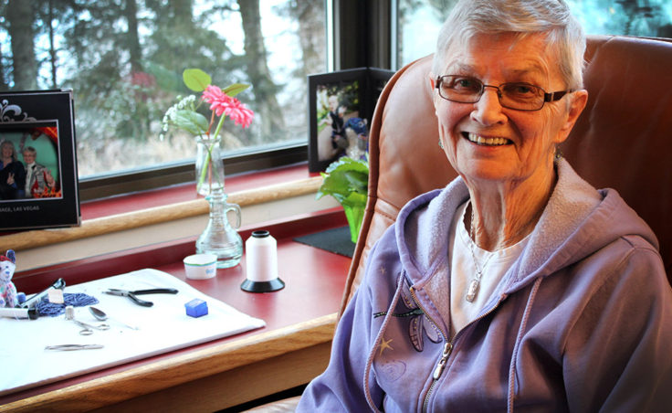 Irene Cashen sits in her room at the state-run Juneau Pioneers' Home. One of her hobbies is beading. (Photo by Lisa Phu/KTOO)