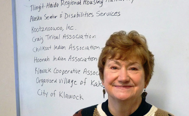 Southeast Senior Services Director Marianne Mills poses with a partial list of other organizations it works with. (Photo by Ed Schoenfeld/CoastAlaska News)