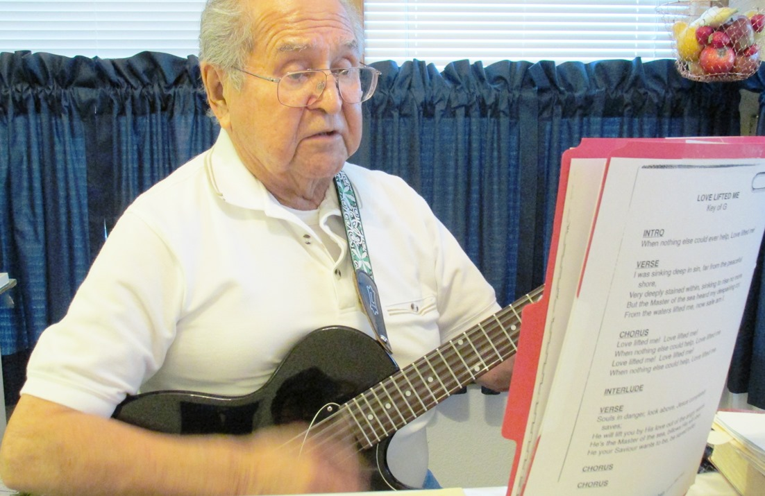 FOR COAST Elder Fred John sings and plays a gospel song in his kitchen. (Photo by Leila Kheiry-KRBD)