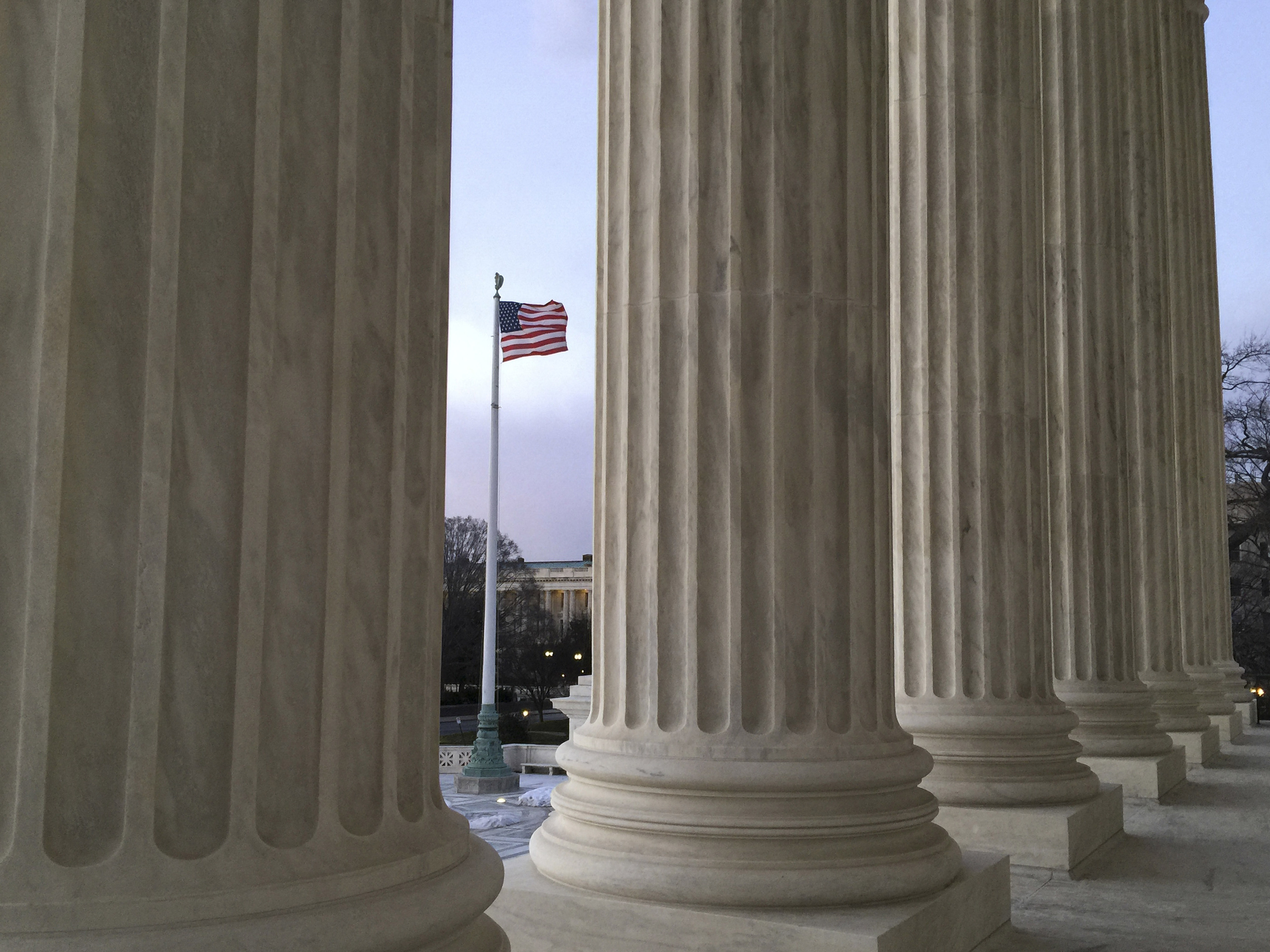 The American flag, seen through the columns of the Supreme Court building, blows in the wind on Feb. 13. (Jon Elswick/AP)