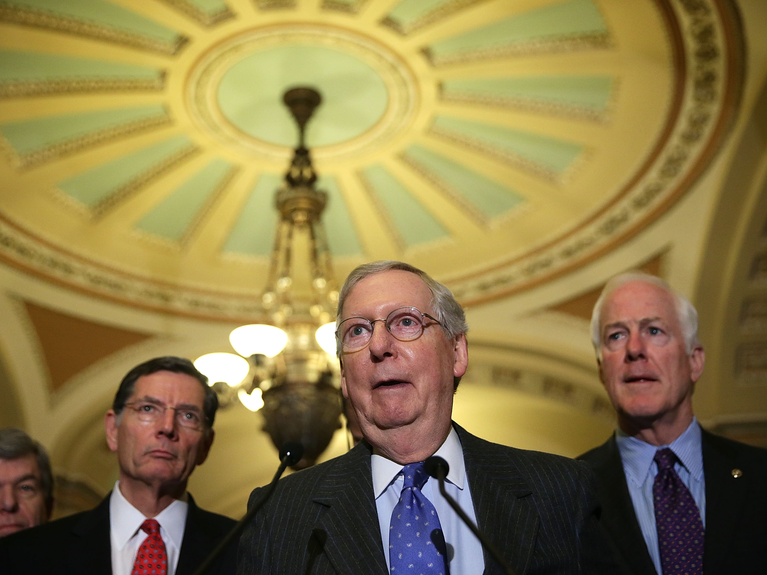 Senate Majority Leader Mitch McConnell (center), R-Ky., speaks to members of the media as fellow Republican Sen. John Barrasso of Wyoming (left) and Senate Majority Whip John Cornyn of Texas (right) listen after the Republican weekly policy luncheon on Jan. 20. (Alex Wong/Getty Images)