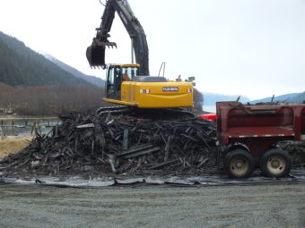An excavator loads truck trailers with the woody remnants of the tug Challenger for the trip to the Juneau landfill.