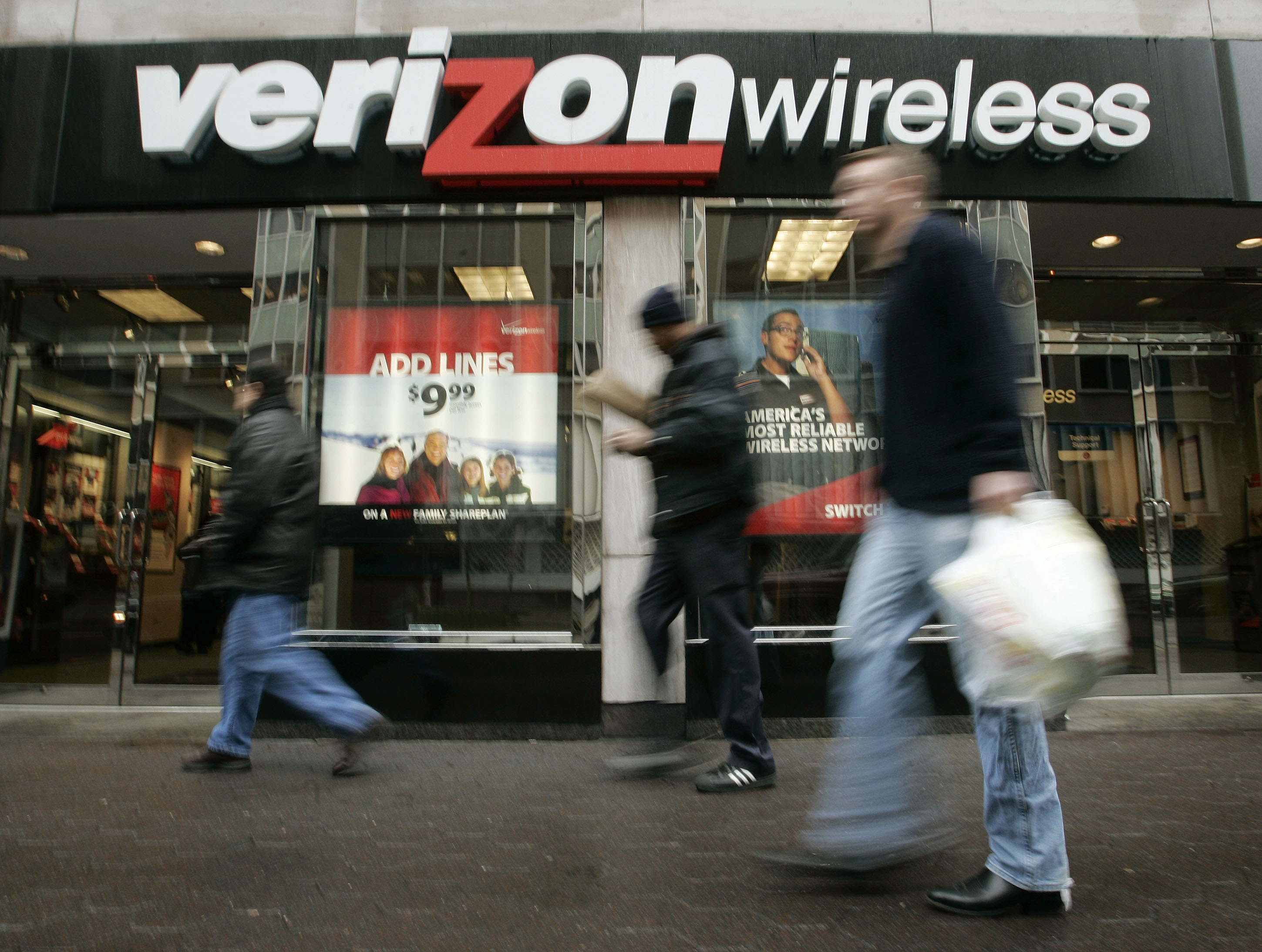 Pedestrians walk past a Verizon Wireless shop. Charles Dharapak /AP