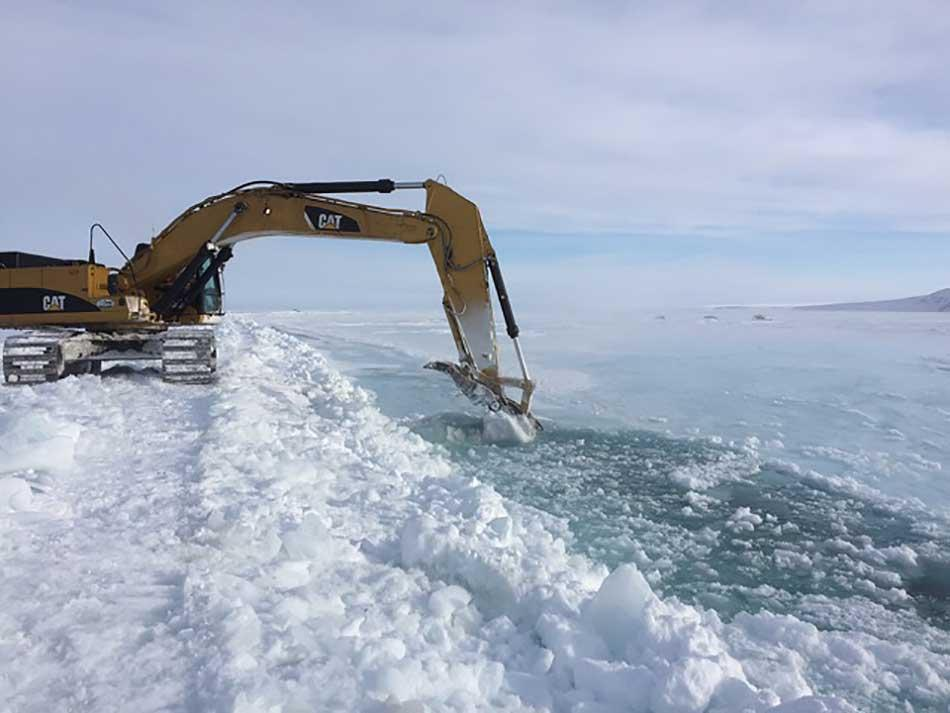 Excavators dig trenches up to 5 feet deep to channel water from the Sagavanirktok River away from the northernmost stretch of the Dalton Highway. (Photo courtesy of Alaska Department of Transportation)