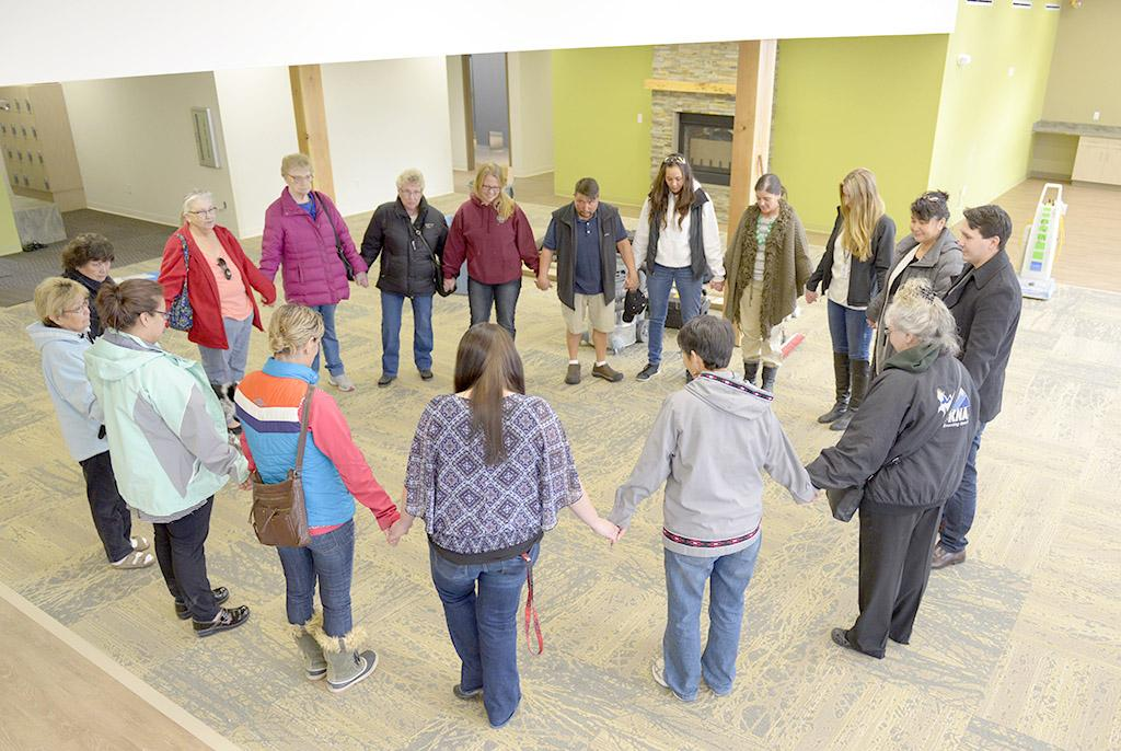 Sharon Isaak (bottom right, grey jacket) leads members of the Kenaitze Indian Tribe's Elders Committee in a closing prayer after the group toured for the first time the tribe's new Elders building on Feb. 11, 2016. (Photo by Scott Moon/Kenaitze Indian Tribe)