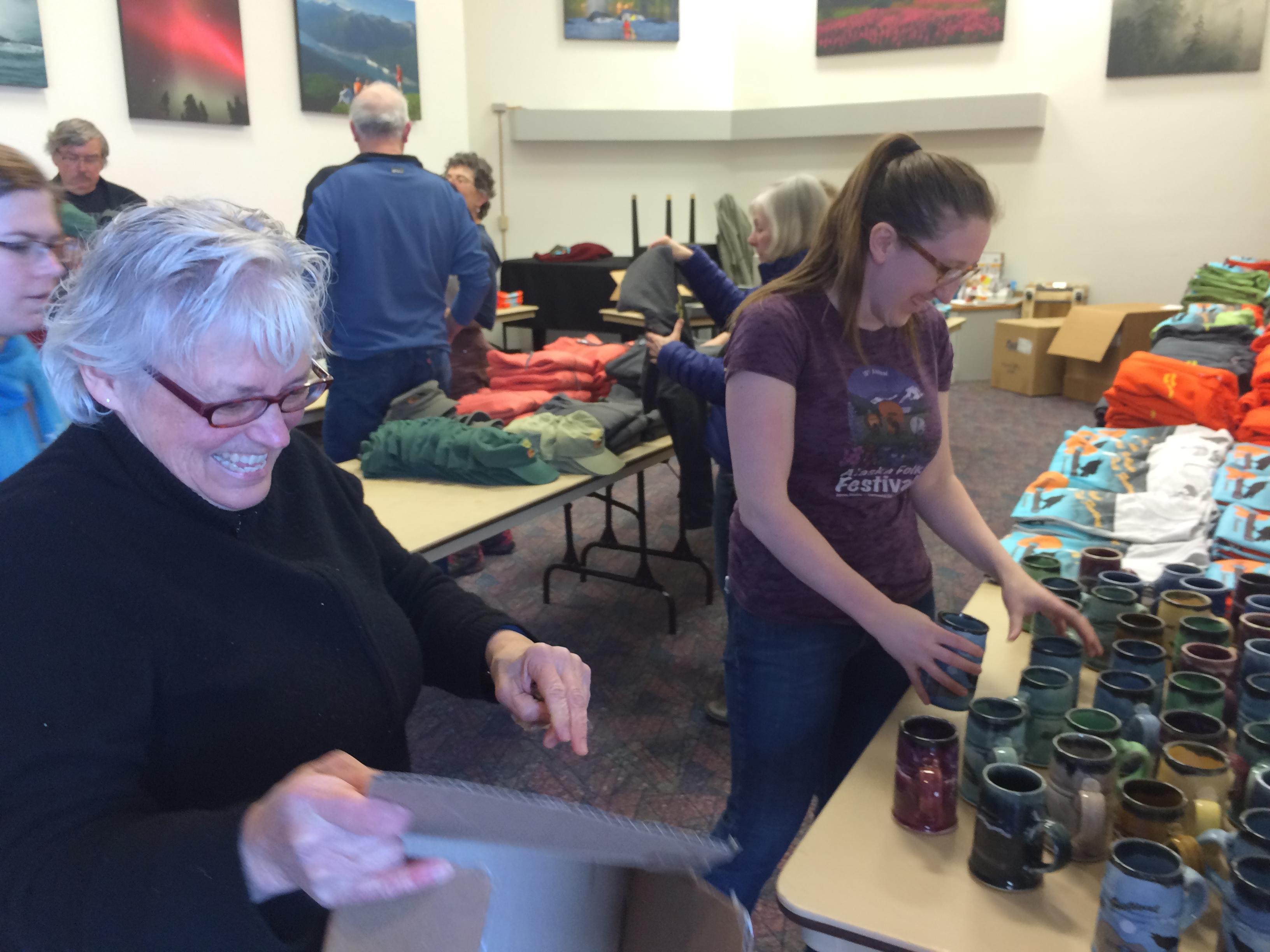 Carol Ackerman and Erin Hanson set up the merchandise table on Sunday. (Photo Scott Burton/KTOO)