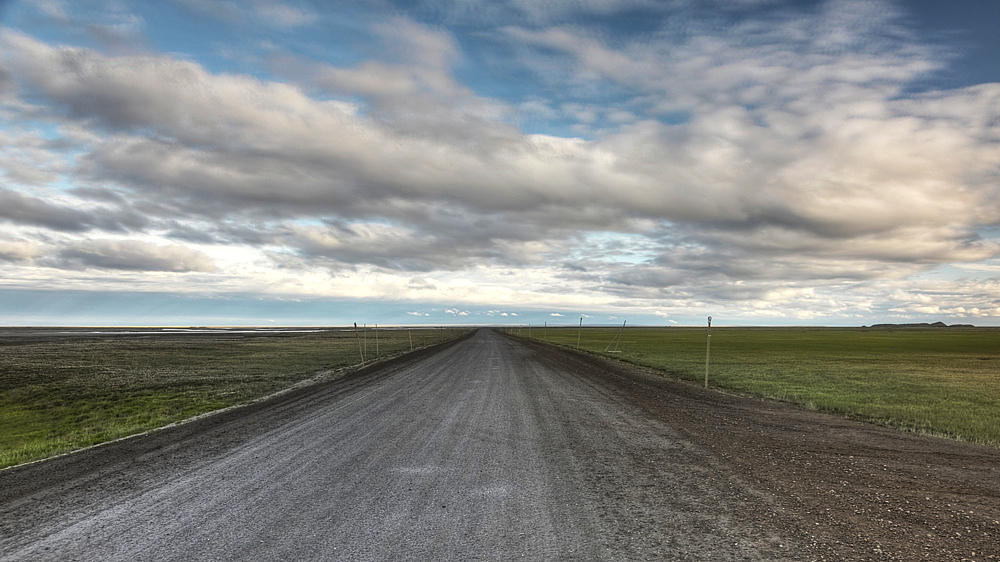 Technologies used to preserve permafrost under roads around Fairbanks may within a few decades be better-suited for areas farther north, such as the 414-mile Dalton Highway, which stretches off to the south in this photo taken near its northern terminus at Deadhorse. (KUAC file photo)