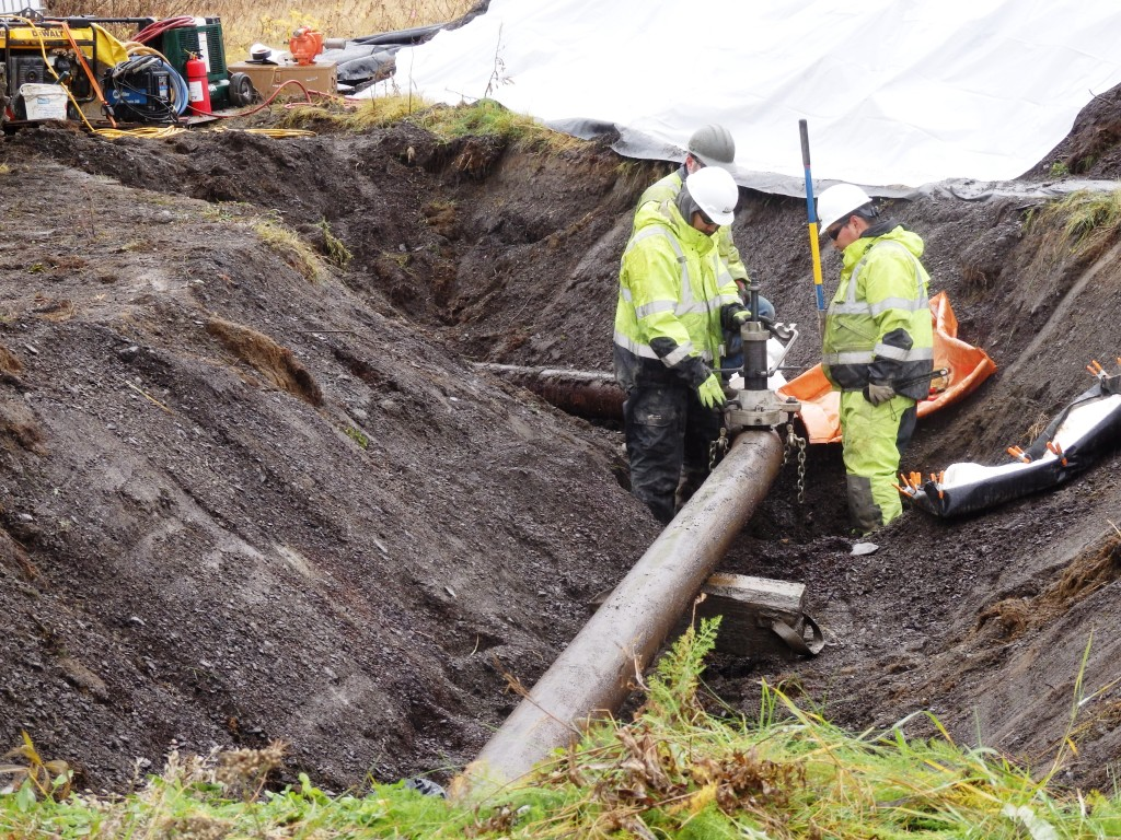 Workers test for residual fluid in a section of pipeline at the former fuel terminal. The Army is removing all 15,000 linear feet of pipeline at the fuel terminal as part of the effort to address the long-standing contamination there. (Photo by Emily Files/KHNS)