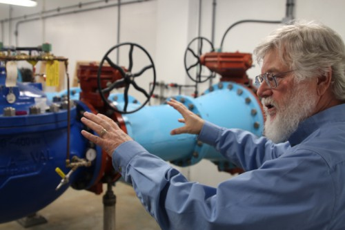 Project engineer Stephen Weatherman explains how all of Sitka's water is run through the 24-inch pipes in the plant. (Photo by Robert Woolsey/KCAW)