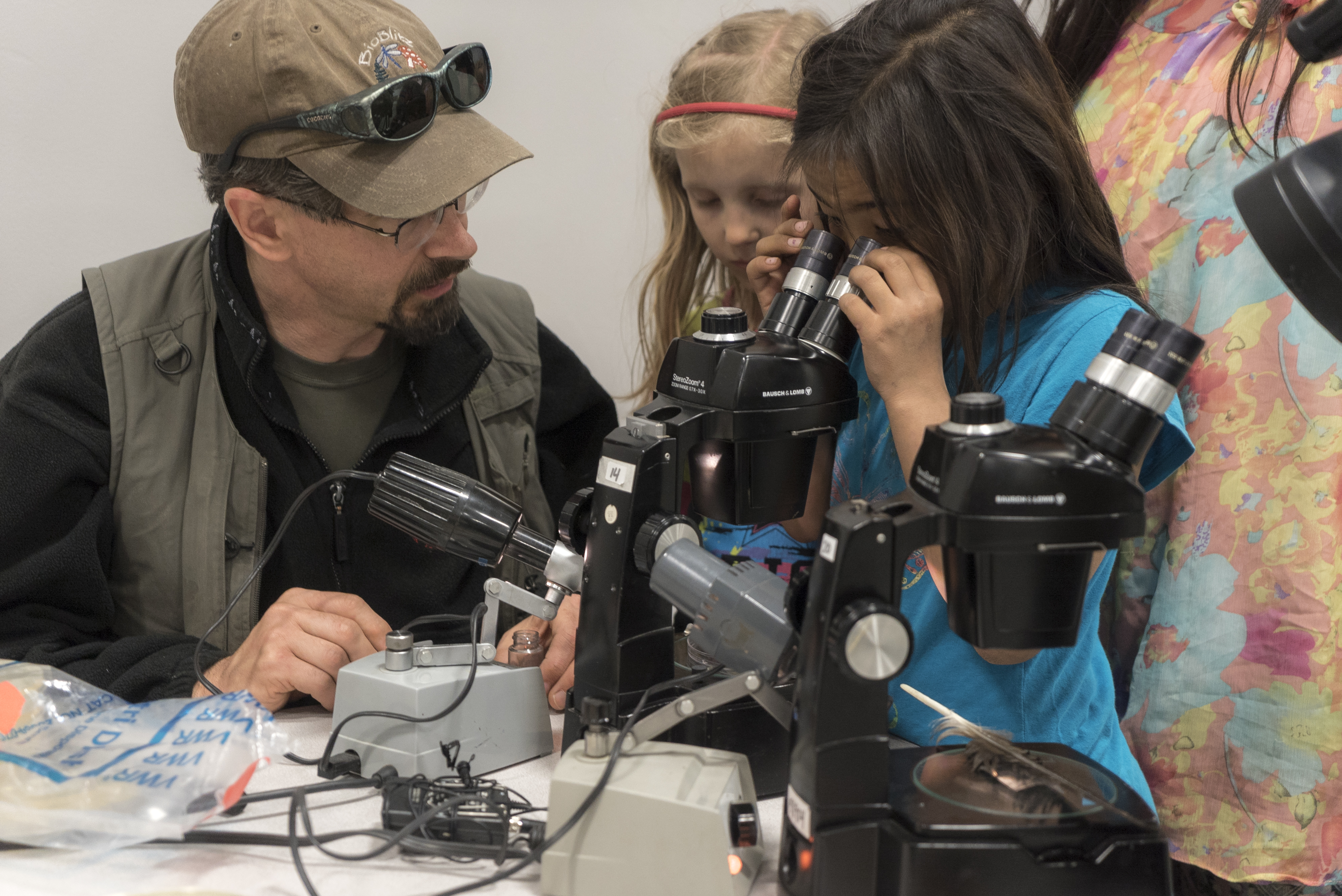 Seven-year-old Anna Nukapigak looks through a microscope at samples. Jeff Rasic and the rest of the students look on.