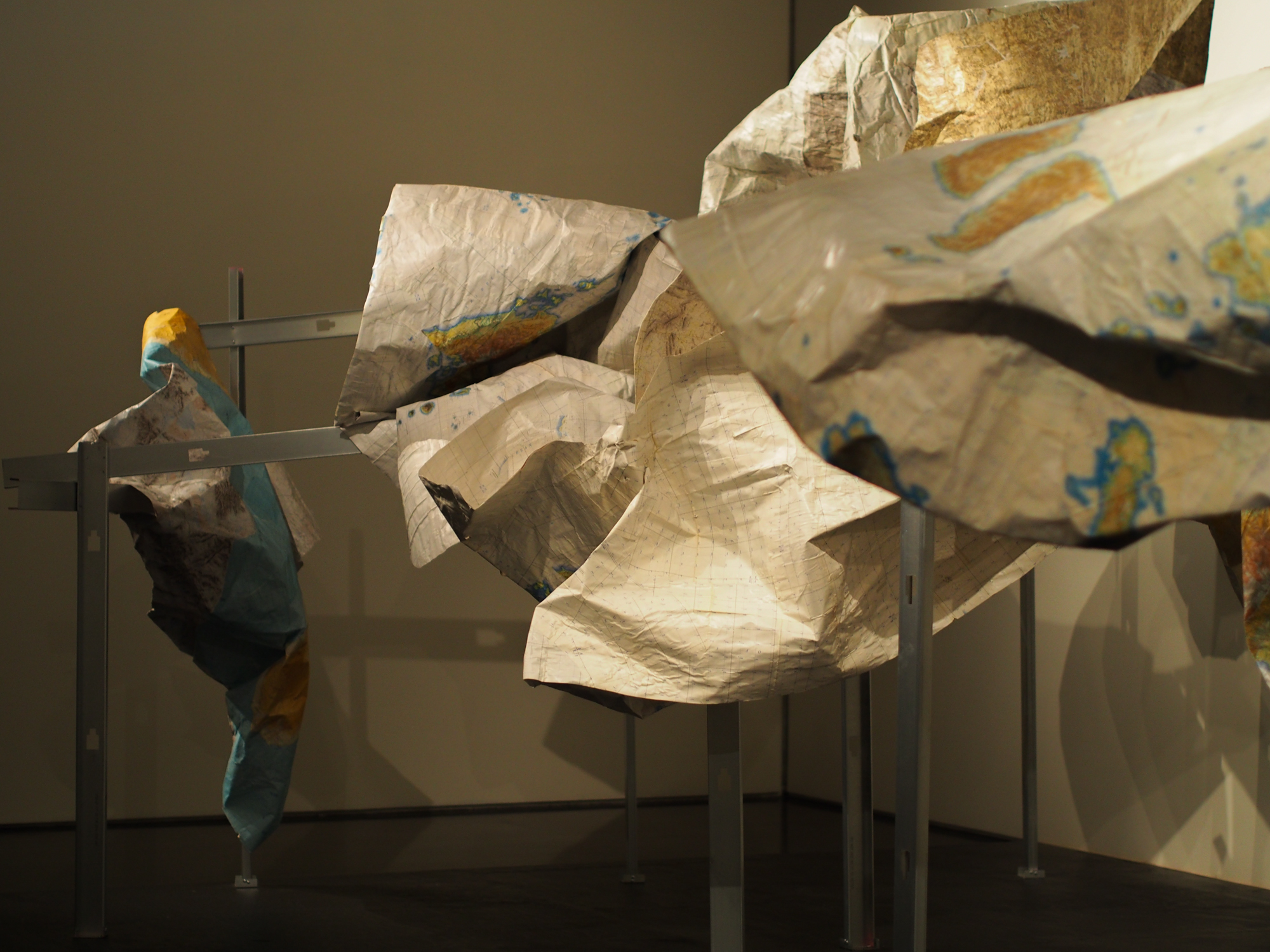"""""""Subsistence,"""" a sculpture by Marek Ranis from old military maps suspended on metal fish racks, part of the Anchorage Museum's """"The View From Up Here"""" exhibit. (Photo Zachariah Hughes/Alaska Public Media)"""