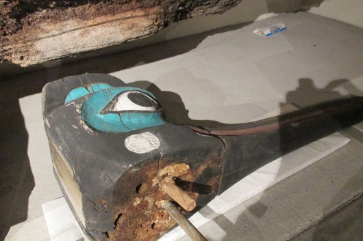 A large fragment from the Chief Kyan Totem Pole showing a metal rod repair. (Photo by Maria Dudzak/KRBD)
