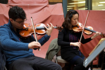Vega String Quartet members Domenic Salerni and Jessica Shuang Wu play violin at the State Office Building Atrium during a Brown Bag Concert as part of the Juneau Jazz & Classics Festival on Monday, Mar. 9. (Photo by Annie Bartholomew/KTOO)