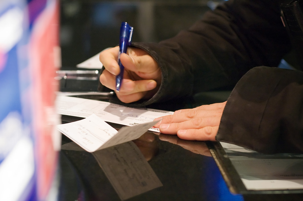 A man fills out a deposit slip at the bank.