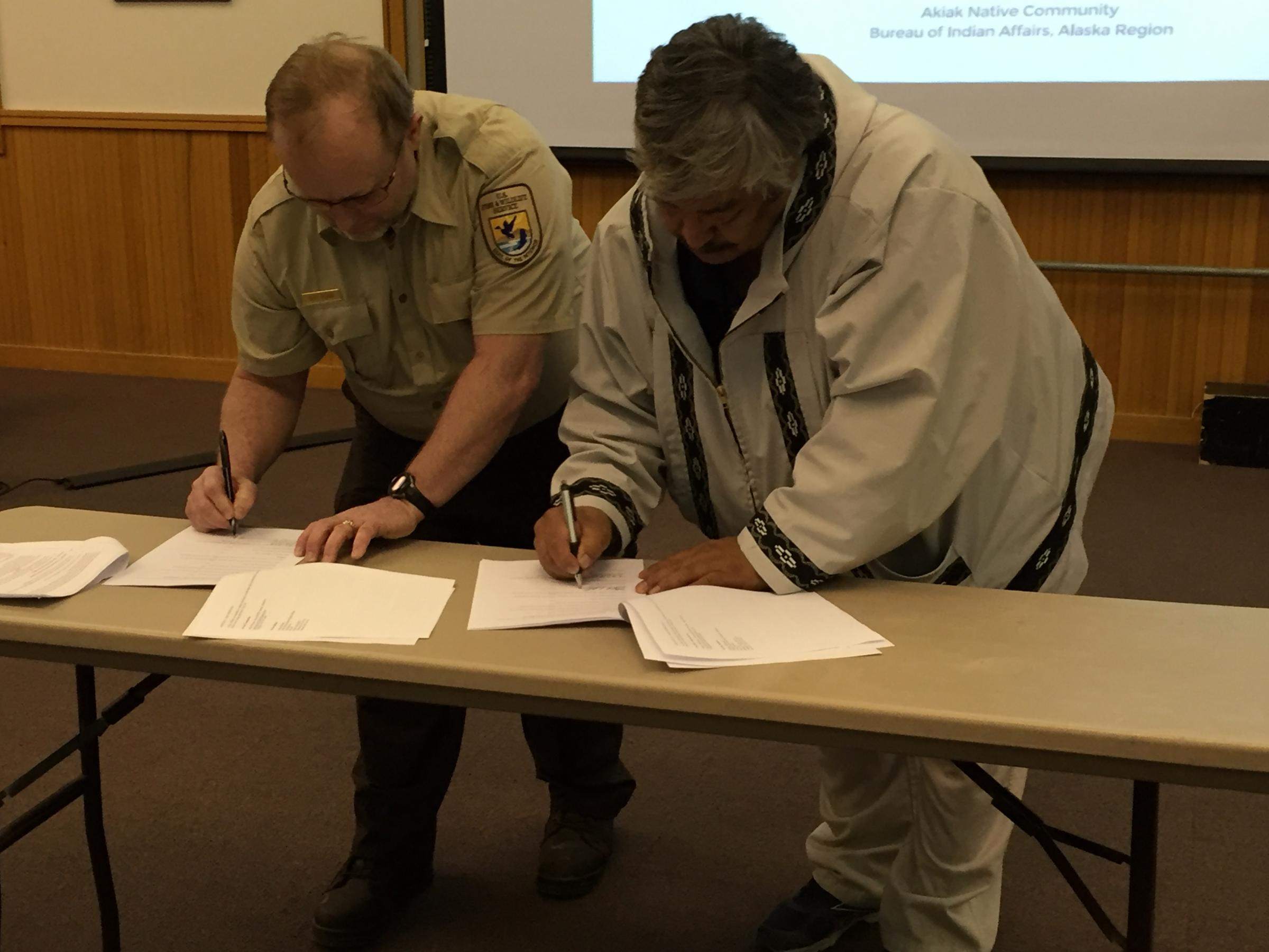 Chair Mike Williams Sr. signs the MOU with USFWS Yukon Delta Refuge Manager Ray Borne. (Photo by Charles Enoch/KYUK)