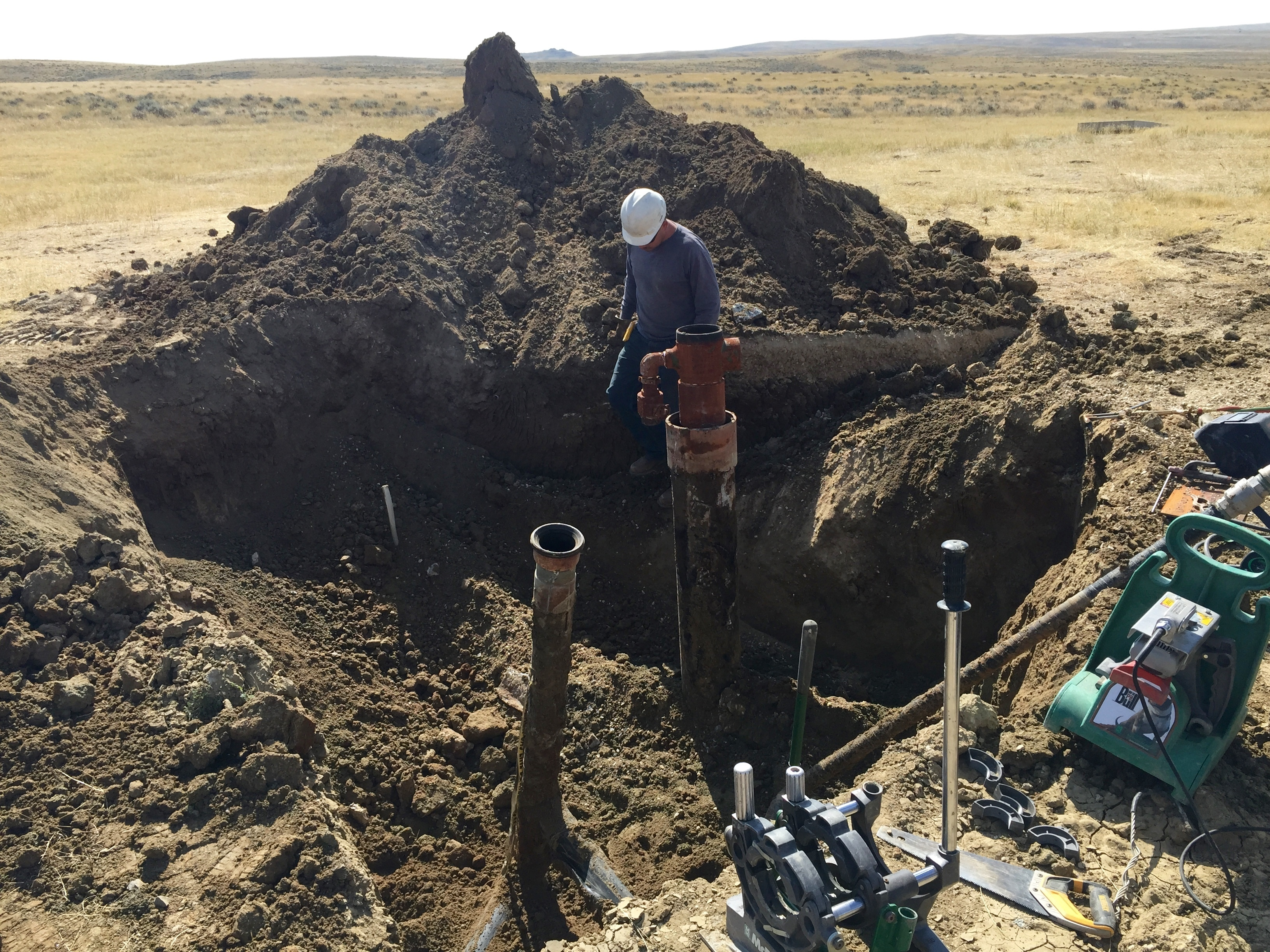 A contractor prepares to cut off the top of a coal bed methane well near Gillette, Wyo., in 2015. It's one of thousands of abandoned, plugged wells sprinkled throughout Wyoming and Colorado. (Photo by Stephanie Joyce/Wyoming Public Media)