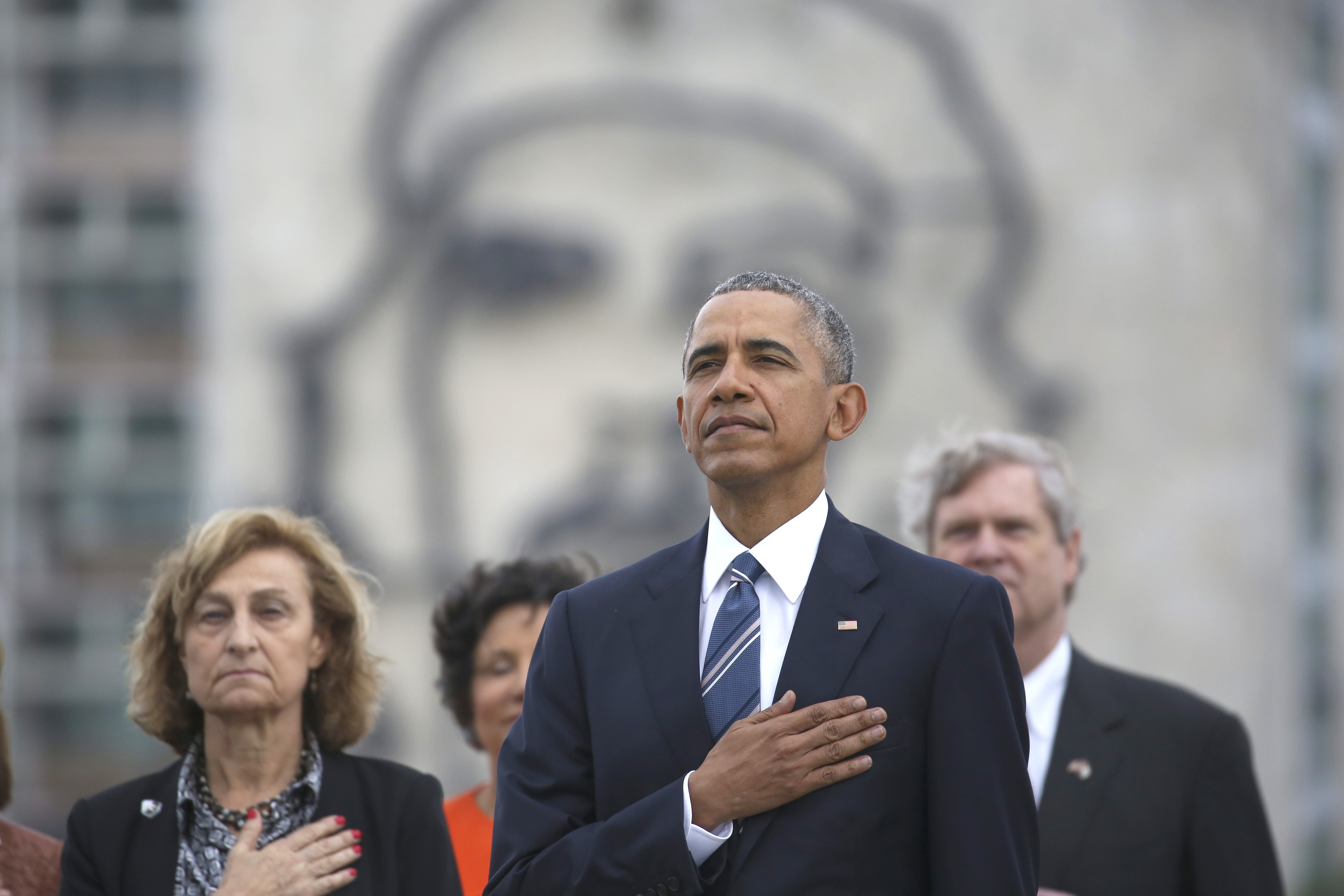 "President Obama listens to the U.S. national anthem in Havana on March 21. Behind him is an image of Cuba's revolutionary leader Ernesto ""Che"" Guevara. (Photo by Dennis Rivera/AP)"