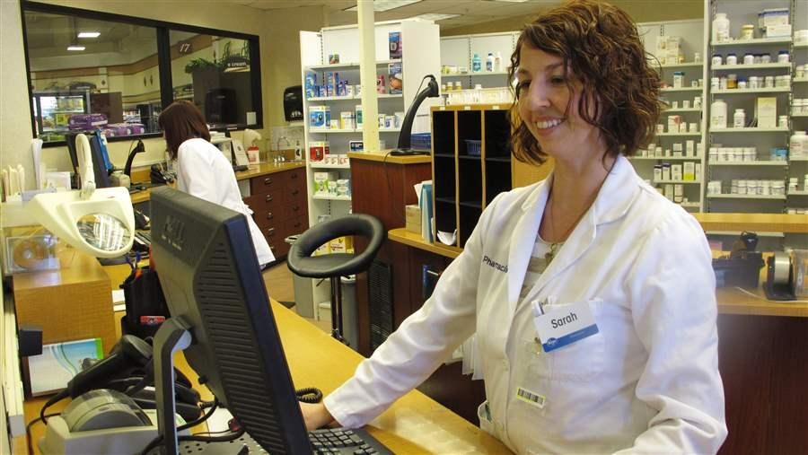 Pharmacist Sarah Burke checks a prescription drug database in Columbus, Ohio, to see whether the patient may be taking any controlled substances. Ohio is one of 16 states that have recently required physicians and other prescribers to run the same type of query before prescribing opioid pain medications. AP