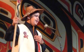 Youth Spokesman Matthew Wesley asks the Celebration audience for a Hoo-Ha cheer during the Taku Kwaan performance. (Photo by Ed Schoenfeld/CoastAlaska News)
