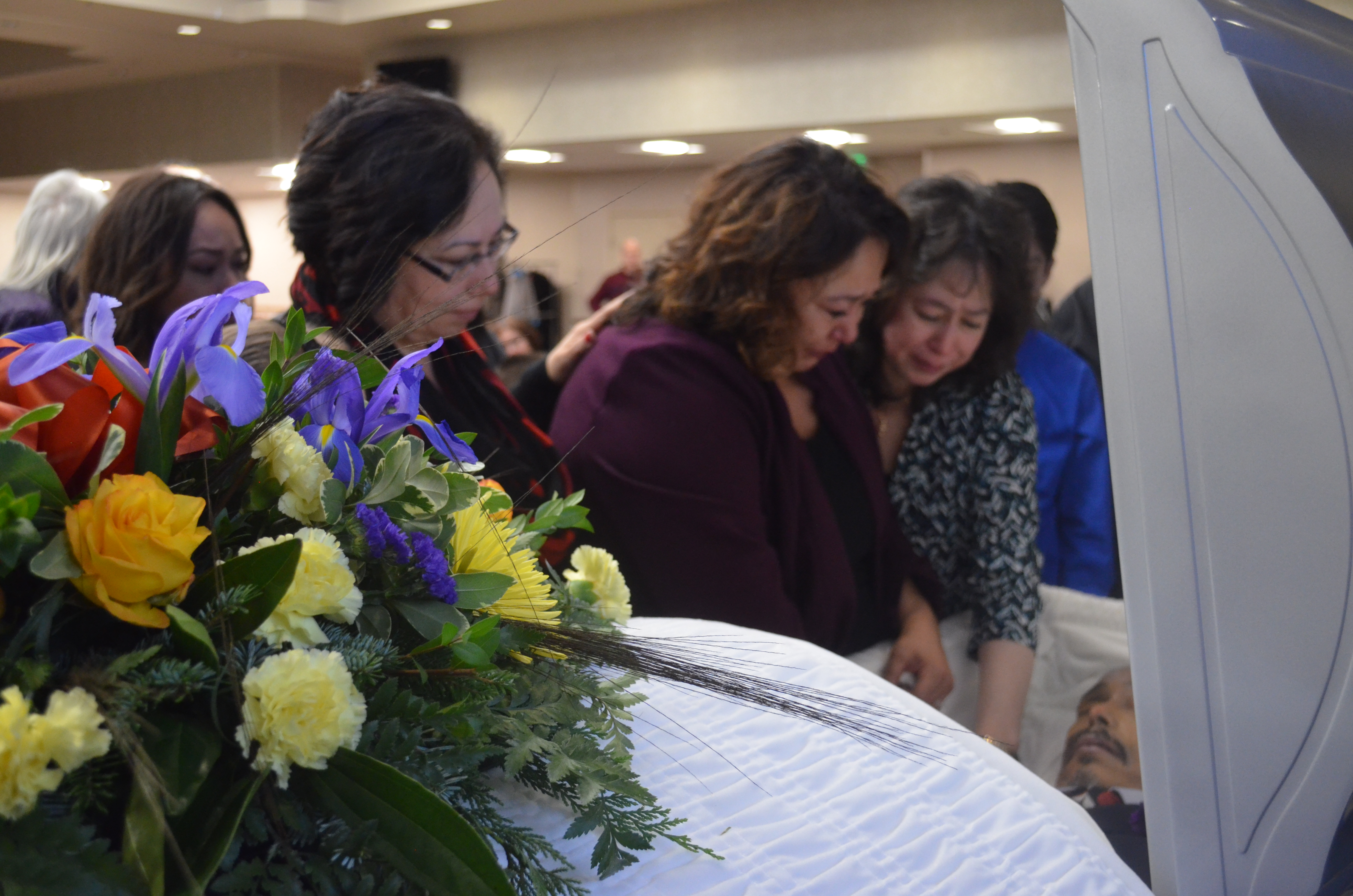 Victoria Canul Dunne (left) and Janine Canul (center) mourn the loss of their brother Mark Canul at his Jan. 26 memorial. (Photo by Jennifer Canfield/KTOO)
