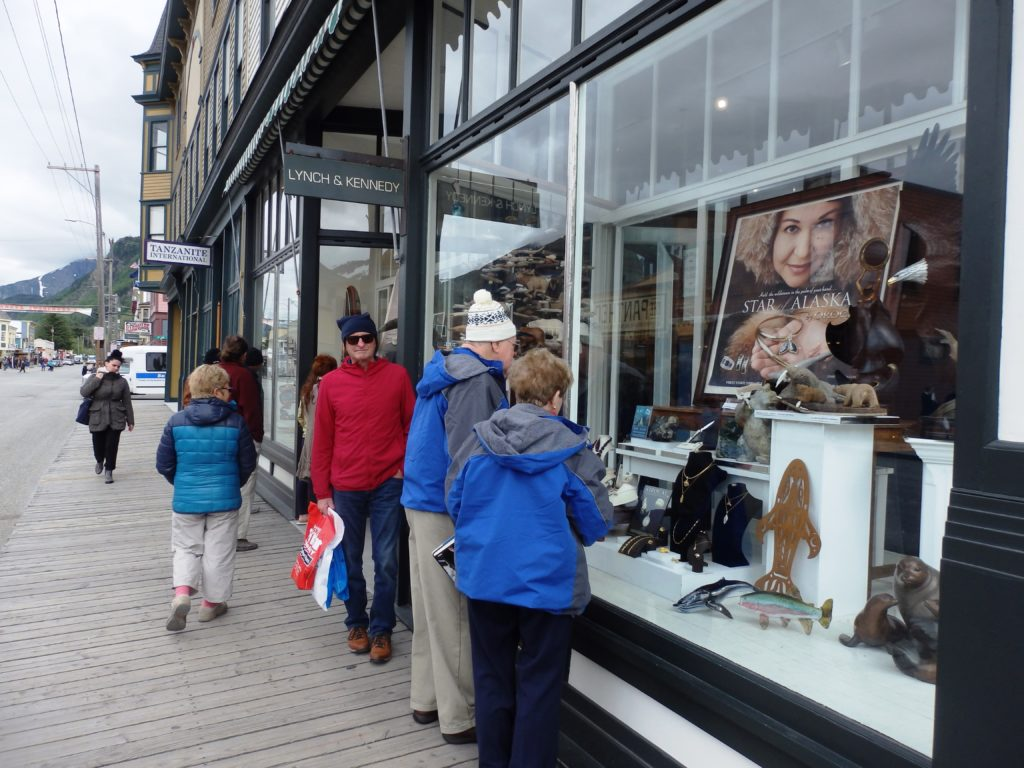 Tourists look in the window of Lynch and Kennedy Dry Goods in May 2016. (Photo by Emily Files/KHNS)
