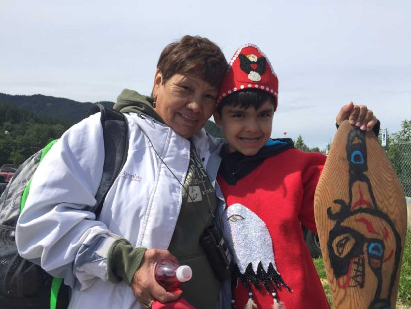 Marie Johnson greets her 10-year-old grandson, Roary Earl Bennett, who just completed a 3-day paddle from Coghlan Island to Douglas for Celebration 2016. Johnson made Bennett's tunic out of felt and abalone shells. (Photo by Emily Kwong/KCAW)
