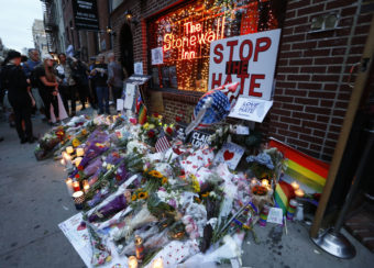 People gather to look at a makeshift memorial for victims of the Orlando nightclub shootings in front of the historic Stonewall Inn, a gay bar in the West Village, on June 13, in New York. Kathy Willens/AP